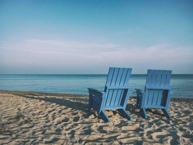 uitzicht op het strand. Twee stoelen waarbij mensen kunnen genieten van het zeewater